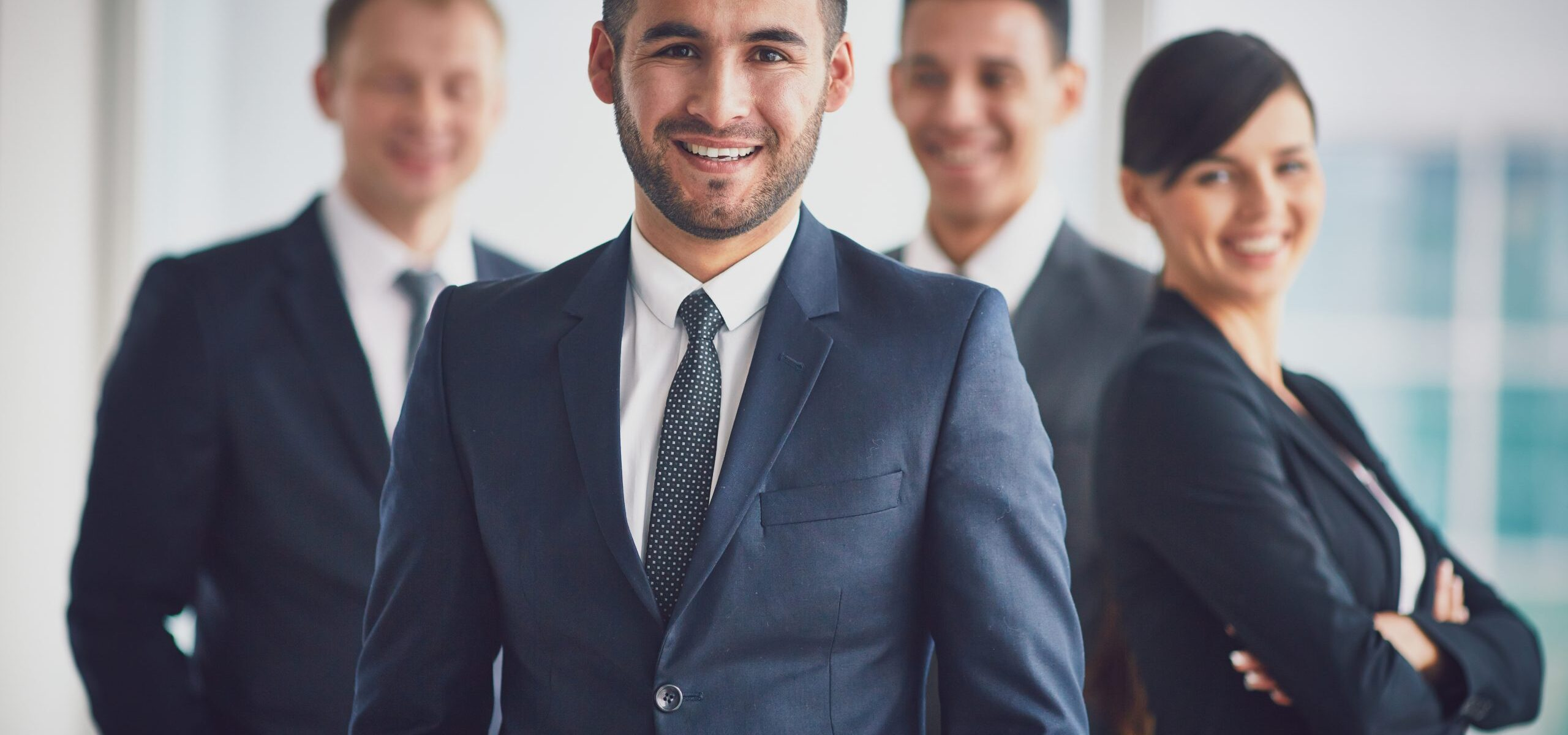 Portrait of confident business partners looking at camera with smiling leader in front